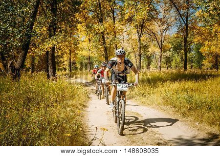 Gomel, Belarus - August 9, 2015: Group of mountain bike cyclists riding track at sunny day, healthy lifestyle active athlete doing sport.