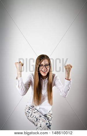 Rejoicing young woman in white. Success and winner concept.
