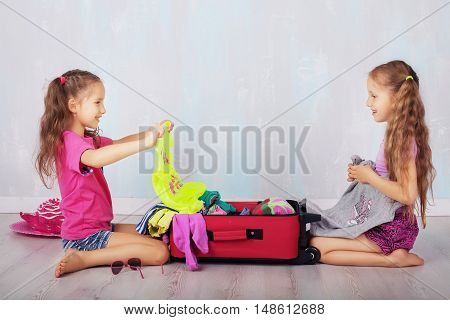 Children collect clothing in suitcase. The concept of travel and lifestyle.