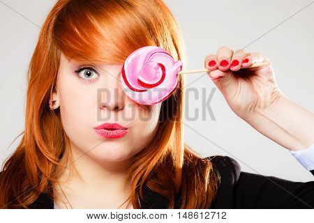 Closeup funny young woman holding candy. Redhair girl with pink lollipop having fun. covering her eye.