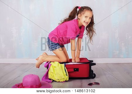 happy little girl sitting on a suitcase