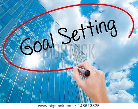 Man Hand Writing Goal Setting  With Black Marker On Visual Screen