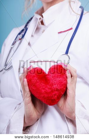 Love from working and helping people. Part body female doctor in white medical apron with heart on blue. Enjoy work concept.