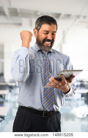 Hispanic businessman celebrating while looking at electronic tablet inside office building