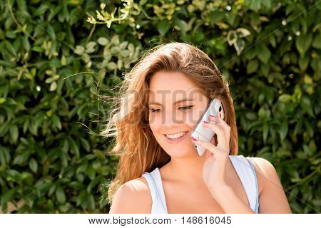 Pretty blonde girl in the park with a mobile