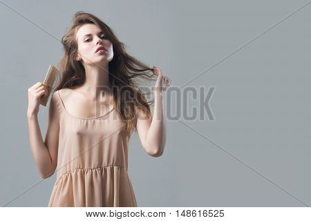 young woman with slim sexy body pretty face and brunette long hair in dress holding hairbrush standing in studio on grey background copy space
