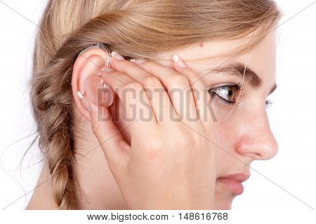 Teen girl inserting a hearing aid. Studio shot-isolated on white background.