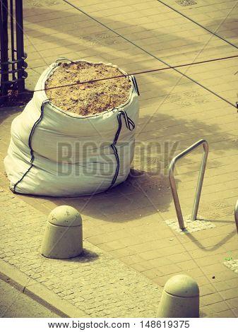 Civil engineering public works building construction concept. Bag of sand on sidewalk. Pavement fragment wirh bike parking.