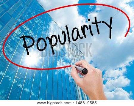 Man Hand Writing Popularity With Black Marker On Visual Screen.