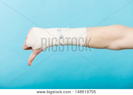 Bad news and information. Medicine aspects. Male hand with bandage showing thumb down sign symbol.