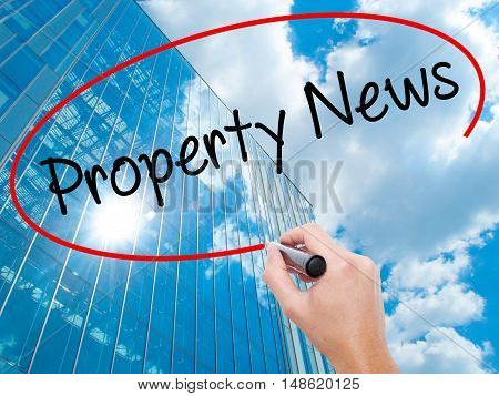 Man Hand Writing Property News With Black Marker On Visual Screen.