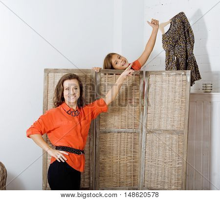 happy mother with daughter trying on dresses at home interior, helping to choose each other, lifestyle real modern people concept close up