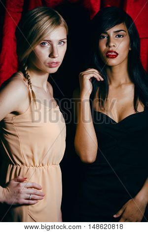 brunette and blond woman together friends, conflict of types on red curtain background, besties forever, lifestyle people concept close up