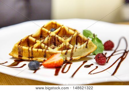Viennese Waffles Drizzled With Chocolate Sauce  Berries On A