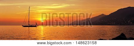 Panoramic view of Sailing at orange sunset with mountains