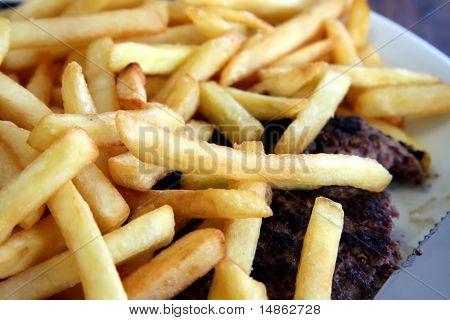 French fries piled on top of cooked hamburger steak