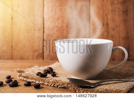 Coffee cup with coffee bean on brown wooden table in still life and dark filter color tone