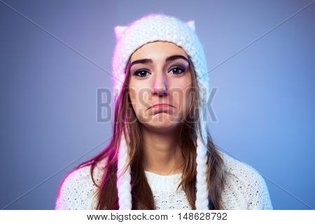 Young sad woman in warm winter white clothing on blue background