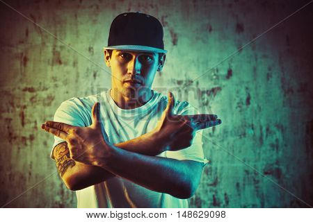 Young man break dancer portrait on wall background. Blue and yellow colors tint. Tattoo on body.