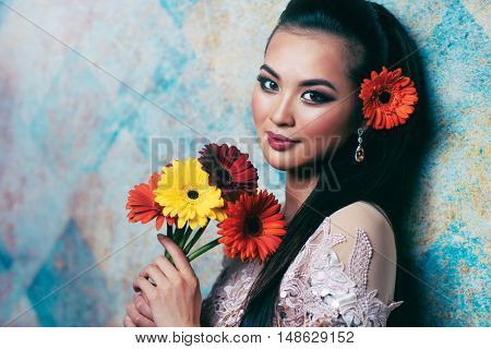 Young asian woman with flowers romantic portrait in bright white colors