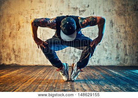 Young man break dancing on wall background. Blue and yellow colors tint. Tattoo on body.