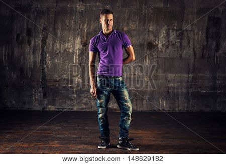 Young man in casual clothing indoors portrait on old wall background