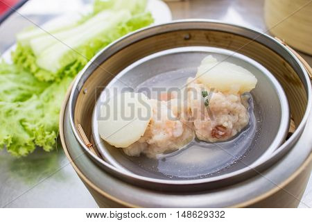dim sum - steamed Minced pork with Scallop in bamboo basket on table blur background