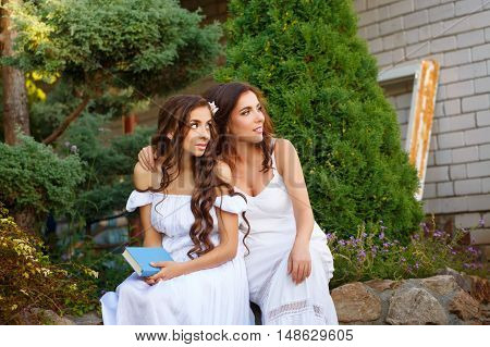 Two sisters. She holding a book and sister hugging her. Girls in long white dress looks aside. Family time in the backyard.