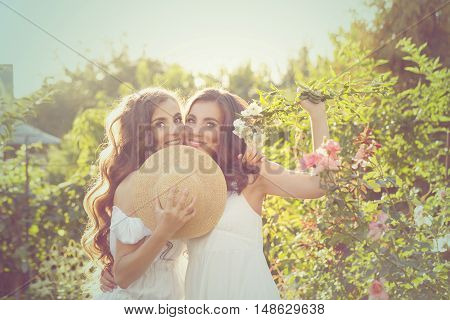Two sisters. Girls embracing in the garden. Family time. Human relationships. Setting sun.