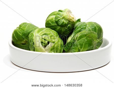 Fresh Brussels sprouts in a bowl on white background