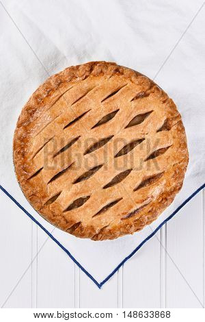 High angle view of a fresh baked apple pie on a white kitchen towel, Vertical format.