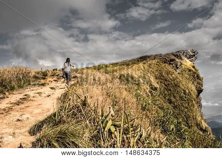 Dramatic nature landscape. Dark tone color of woman walking to the mountain in dark sky. Adventure concept.