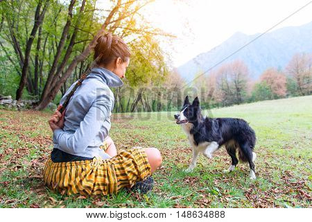 Girl playing with a stick for his dog his border collie