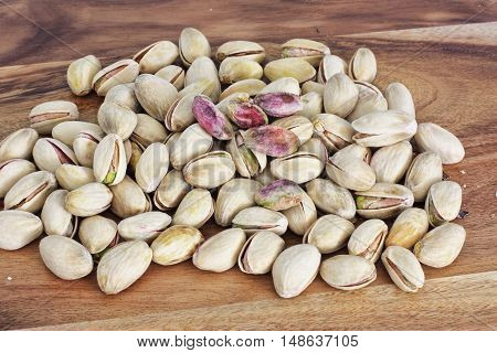 pistachio nuts unhusked on a wooden table