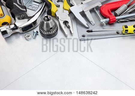 Set Of Hand Tools Including Hammer, Clamp, Screwdrivers And Other On Scratched Metal Background