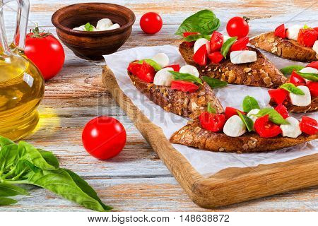 bruschetta with tomatoes mozzarella and basil on fried in olive oil rye baguette with seeds on parchment paper. ingredients on peeling paint white planks italian style close-up