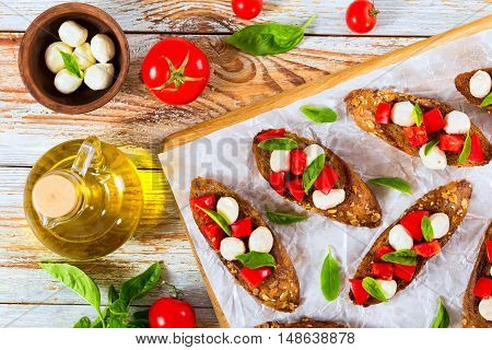 bruschetta with tomatoes mini mozzarella and basil on fried in olive oil rye baguette with seeds bottle with oil tomatoes and mozzarella in small bowl herbs on peeling paint planks top view