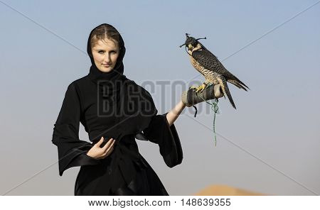 Emirati woman in traditional emirati dress (abaya) with a falcon