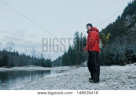 Resting mountaineer with alpinist backpack and equipment is standing on pebble river bank at winter evening rocky landscape background