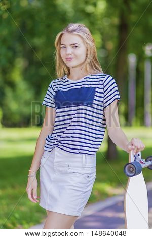 Youth LIfestyle Concepts. Blond Caucasian Teenage Girl Posing With Long Skateboard in Green Forest Outdoors. Horizontal Image Composition