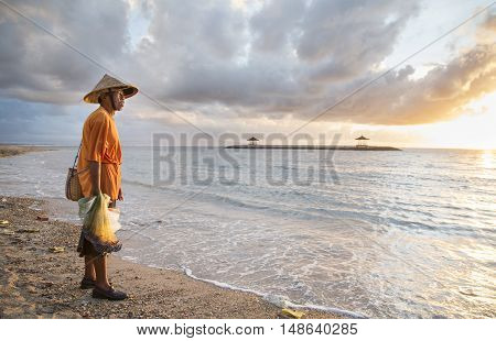 Bali Indonesia September 11th 2016: old fisherman on the beach with his fish nets