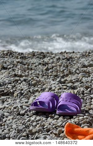 Pair of bright purple beach sandals are on the grey pebble in sunlight.