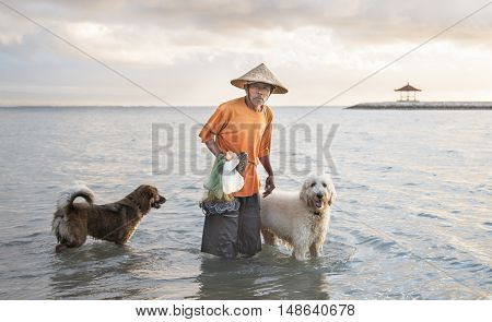 Bali Indonesia September 11th 2016: old fisherman with dogs