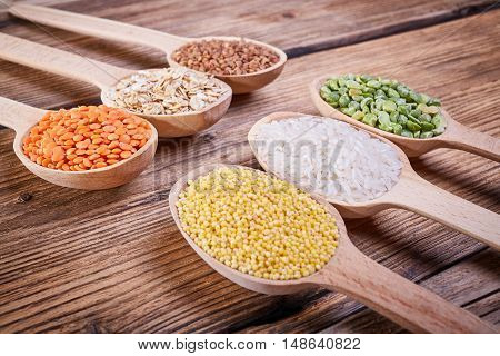 Grains in the spoon, a wooden spoon, a range of cereals, the grain harvest, organic food, cereal close-up, texture of old wood, kitchen utensils, healthy food