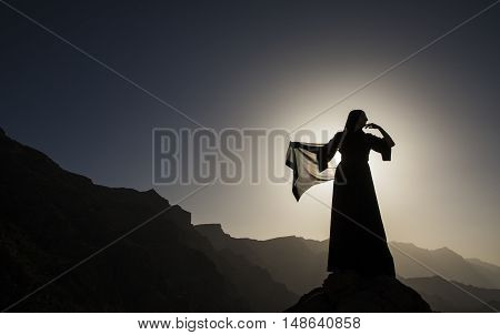 a woman in traditional Emirati dress (abaya) in mountains