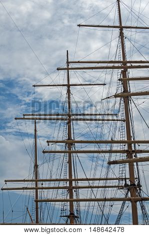 Masts of big sail ship against the cloudy sky background