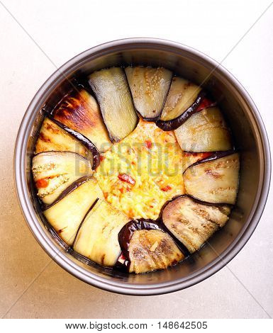 Aubergine timbale - vegetable and cheese bake in a pan before baking top view