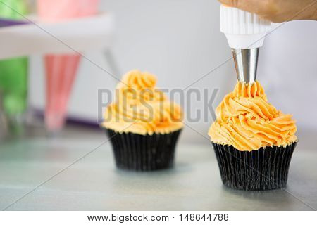 Confectioner decorate some cupcakes with pastry bag