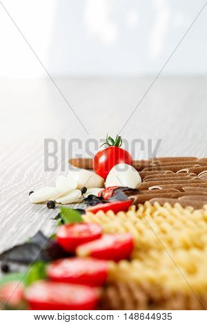 Mixed Of Two Colored Pasta Near Tomatoes, Garlic And Basil On Grey Wooden  Background. Close Up  Raw