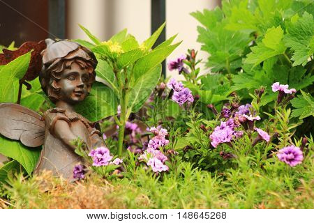 Flower-bed with an angel statue and green plants